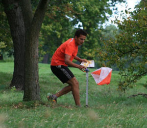 Man approaches marker point whilst orienteering